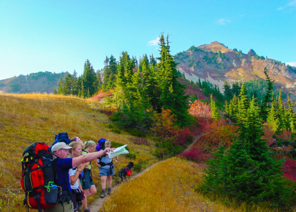 A group of backpackers traversing a ridgeline, pointing out with a map int he distance