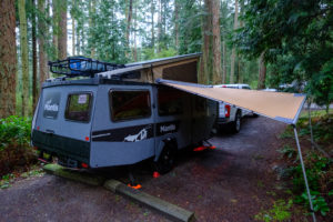 Mantis in a forested campsite on a rainy day with the awning setup