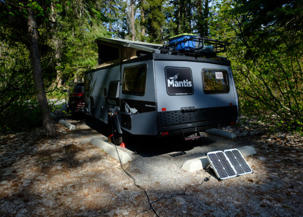 Mantis parked in the trees on a sunny day with a portable solar panel setup