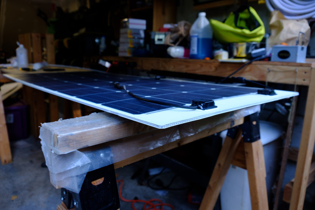 One of the Rangy 160W solar panels on a work table, adhered to the corrugated plastic