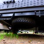 The full sized spare tire of the mantis hanging underneath the back side of the trailer bed