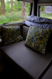 The master bed of the Mantis made into a couch with two throw pillows