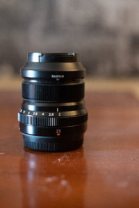 Fuji 23 on a wood table with a blurred black and white picture in the background