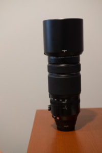 Fuji 100-400 on a wood shelf with an off white background