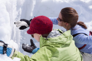 Two women feeling a snow pit for layers of instability