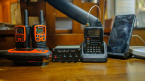 """My home """"shack"""": a Yaesu VX-6R, SignalLink USB iPhone wireless charger, two Midland FRS radios, and a Garmin inReach Explorer. Not pictured are my iPad Pro and MacBook Pro."""